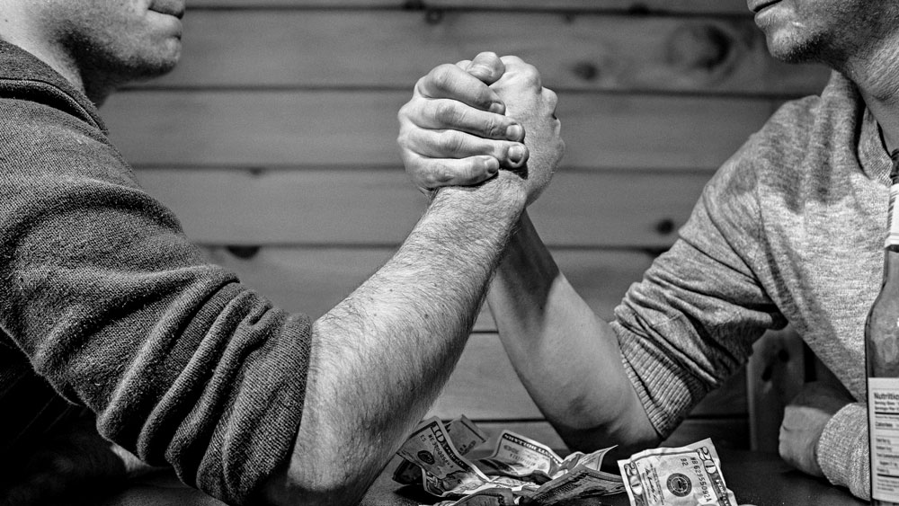 Two gentlemen arm wrestling on a table covered with money, signifying that if you do things correctly in the first place, you won't need to struggle.