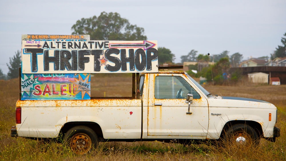 Rusty pickup truck with signs that say alternative thrift shop and super deals, signifying that the quality you receive equates to how much you spend.