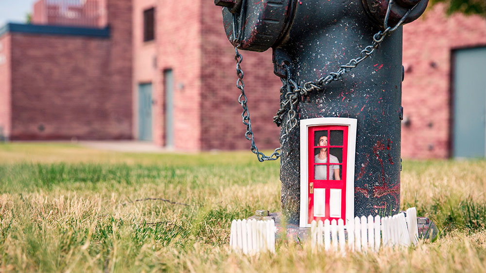 Tiny front door and picket fence on a fire hydrant. Having a front door that is outdated or need of repair can define your home.