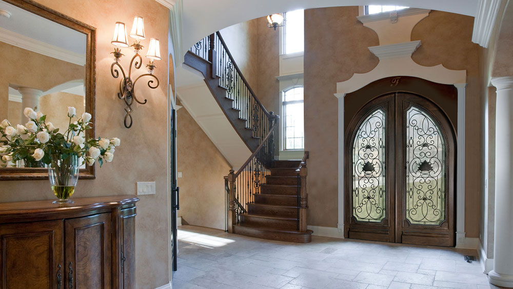 A well appointed traditional interior entryway highlighted by an ornate iron and wood double entry door.