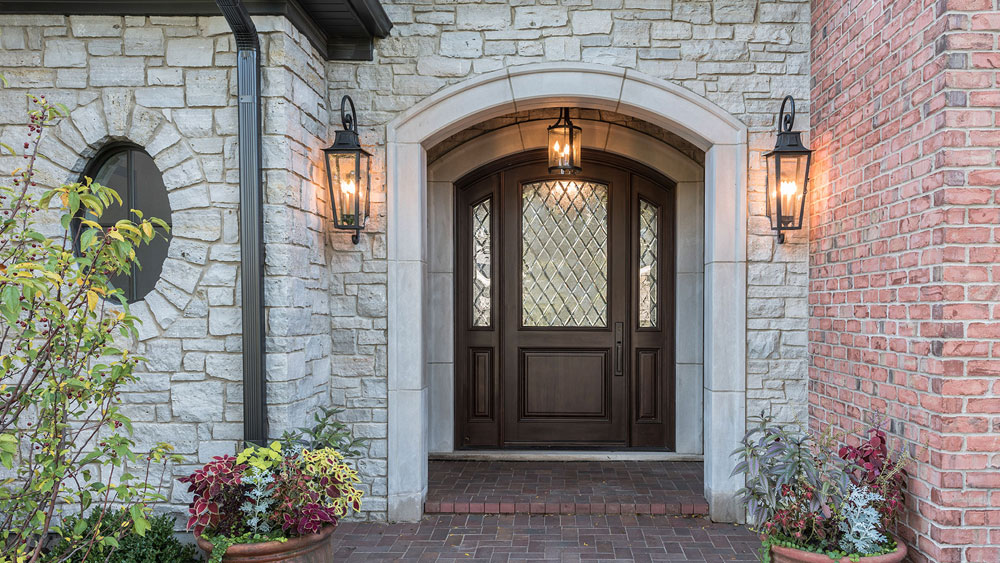 Arch top, single entry wood door with diamond divided lites and coordinating sidelites set into the covered exterior of a stone and brick home