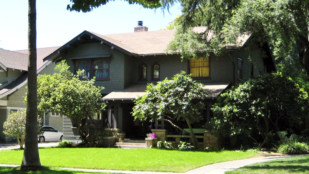 Exterior of the 2-story craftsman with gray-green painted wood shingle siding and a stone porch, movie scene home of Lorraine Baines McFly