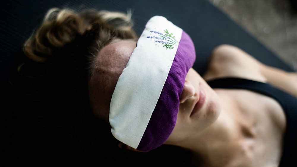 Meditating woman lying on the floor with a lavender mask over her eyes, signifying the importance of insulation and dampened sound in the room