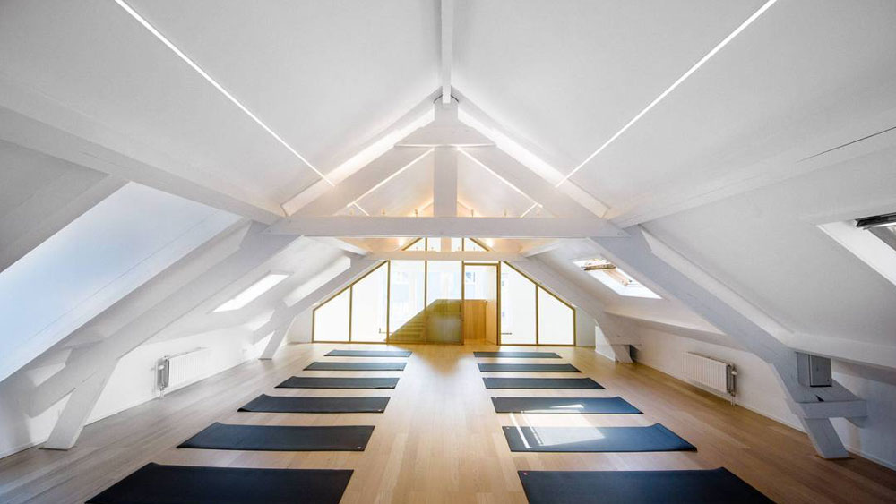 Yoga mats set up in 2 rows on a light wood floor in a long room with a vaulted ceiling and a wall of windows at the head of the room.