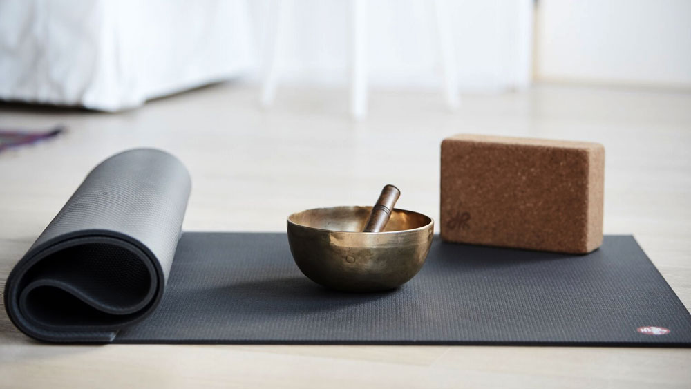 A cork block and Tibetan singing bowl on a dark gray yoga mat, shows the importance of planning for storage space to put tools in your yoga room.