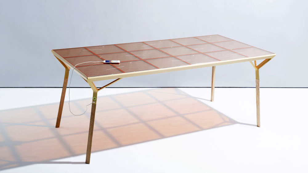 A modern gold frame table dining table with a rose gold glass top, integrated with dye-sensitized solar cells that create electrical current.