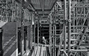 Black and white image of construction of the foundation of a commercial building surrounded by scaffolding, signifying the slowly rising ABI scores.