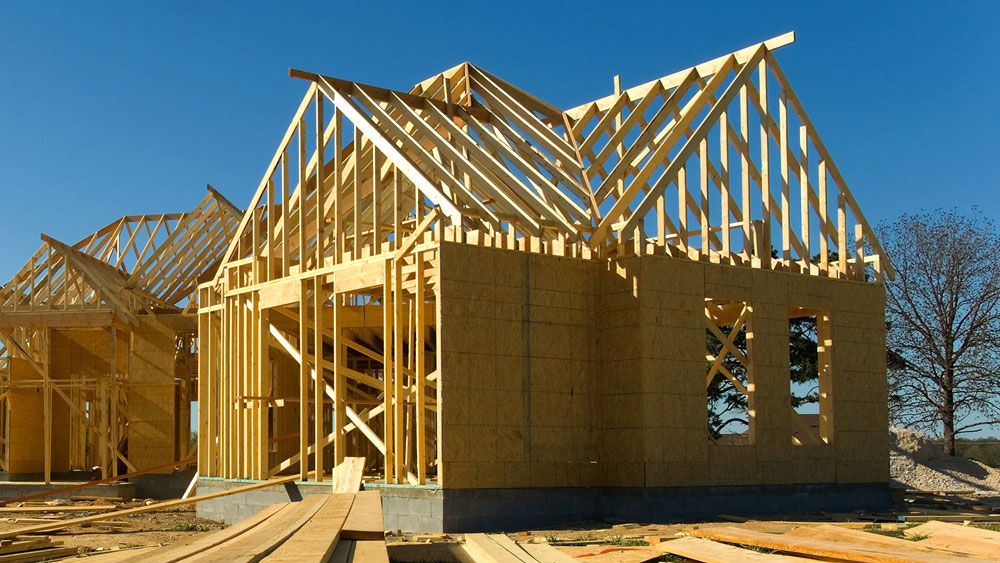 A wood frame of a home under construction that is being covered with OSB as exterior sheathing, which can pose a health risk due to off-gassing.