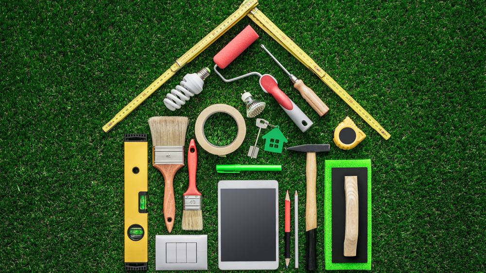 Construction tools laid out in the shape of a house on green grass background, signifying being involved in your home design to calculate VOC exposure