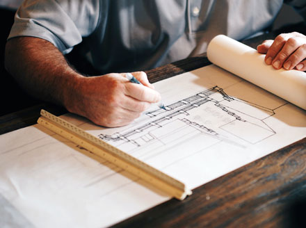 Architect in a gray shirt hand drawing building plans for a railing and staircase on a roll of paper with a ruler