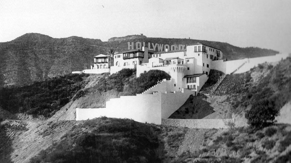 Castillo de Lago home circa 1926 designed by John Delario with a backdrop of the Hollywoodland sign in Los Angeles, California