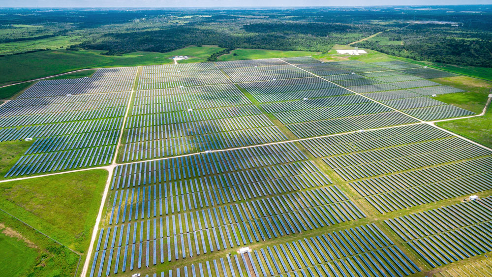 Acres of solar panels comprising a large solar farm in the middle of green pastures