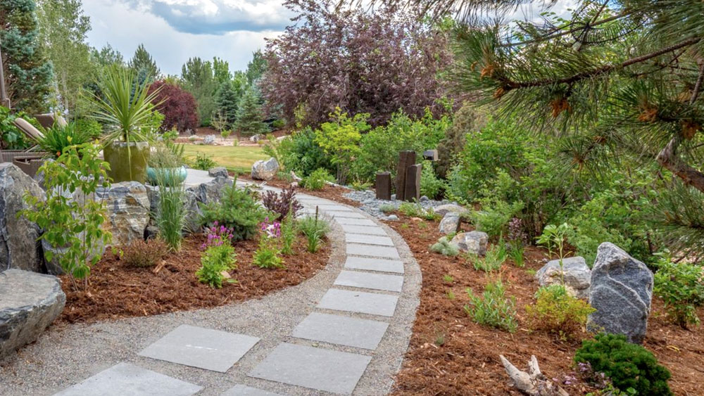 Gray gravel and square paver pathway surrounded by large decorative boulders and wood mulched xeriscape
