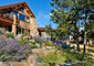 Stone house in Denver surrounded by native trees, large boulders, and xeriscape with a gray gravel pathway
