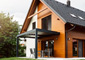A modern passive house with slatted sun shades, black solar roof tiles, wood siding, and a metal overhang to shade the sliding glass door.