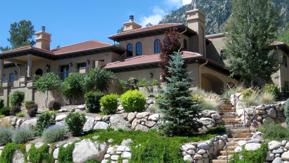 A terraced yard with native xeriscape plantings and large boulders in front of a Spanish revival home in Colorado