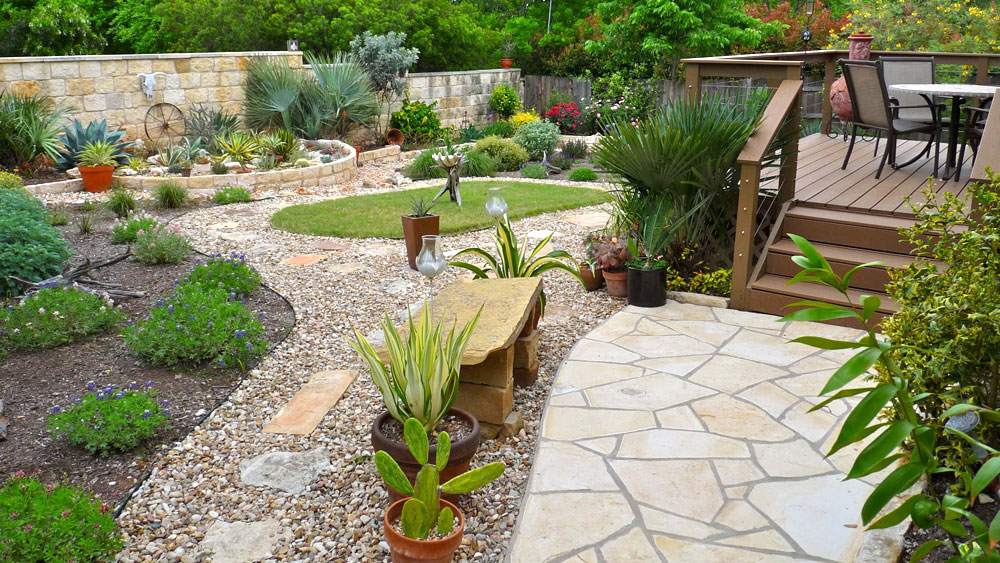 Raised wooden deck surrounded by pebble stone pathways and mulched beds with water-saving plants, signifying the many design options in xeriscaping