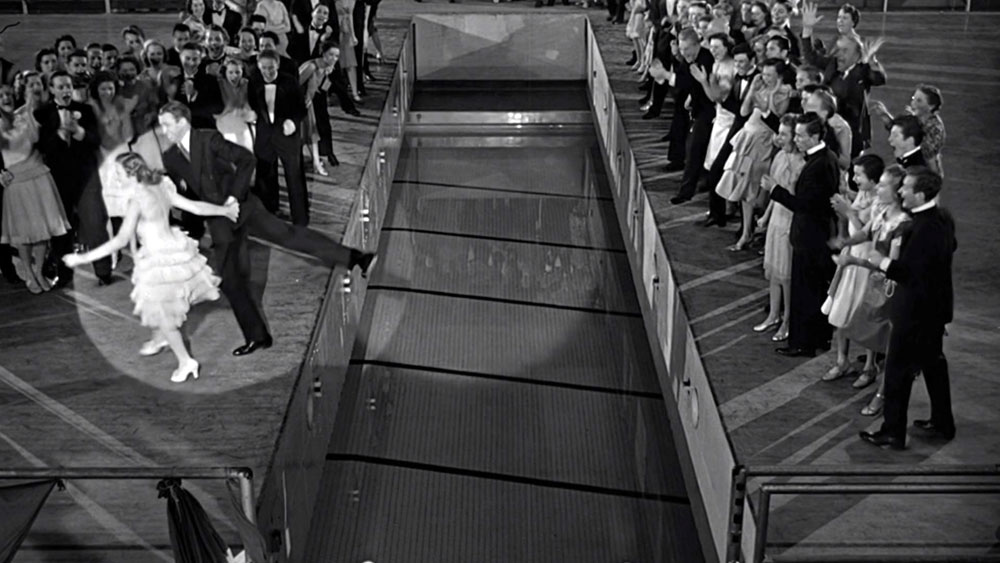 "Jimmy Stewart and Donna Reed dancing on the edge of the retractable gym floor in ""It's A Wonderful Life"", about to fall into the pool"