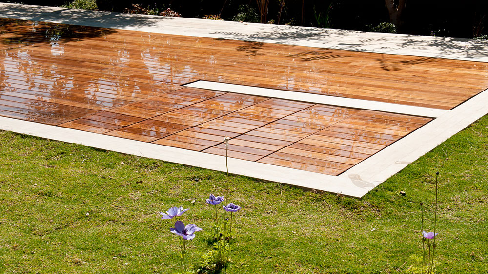 A moveable floor teak pool cover that is closed to create a wooden deck, concealing the rectangular pool beneath