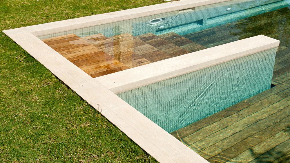 Moveable floor teak pool cover in the open position, revealing pool steps and adjustable depths of the blue tiled pool
