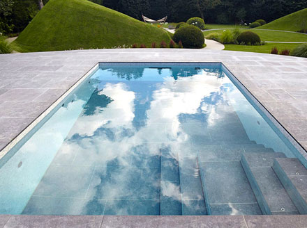 Rectangular pool with tile pool deck and moveable tile floor that serves as a pool cover when closed with green pasture hills in the background