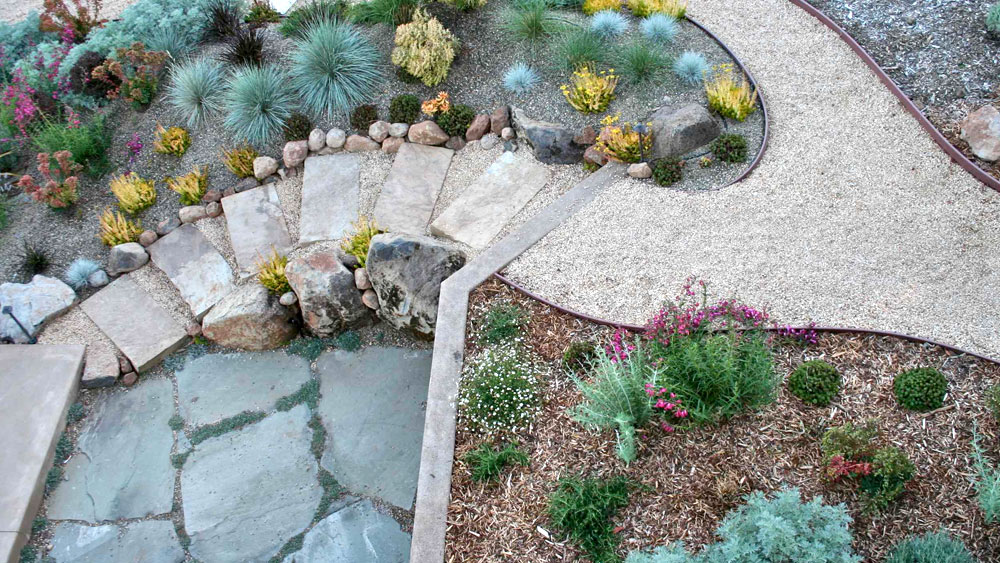 Xeriscaped sloping pathway of crushed gravel between bark and rock mulched xeric beds