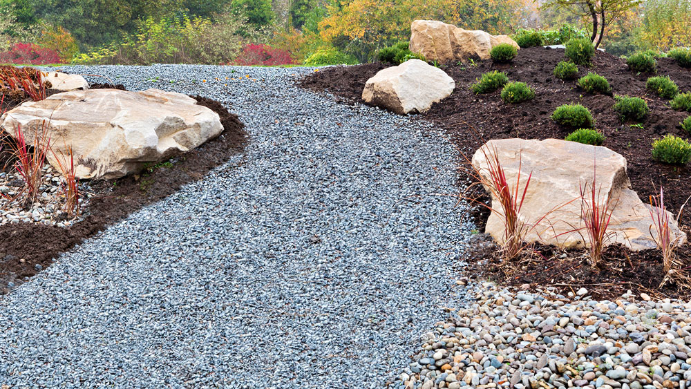 A xeriscape including a pathway of black basalt adjoined to a river rock drainage route, surrounded by dark bark mulched flowerbeds