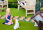 Dollhouse figurines of small girl kneeling in front of a dog and a man on a bench reading a newspaper in an outdoor courtyard