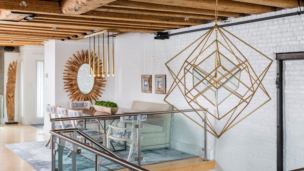 A gold and glass Cubist chandelier by Kelly Wearstler for Visual Comfort hanging in the 2-story foyer of a modern loft from an exposed wood joist.