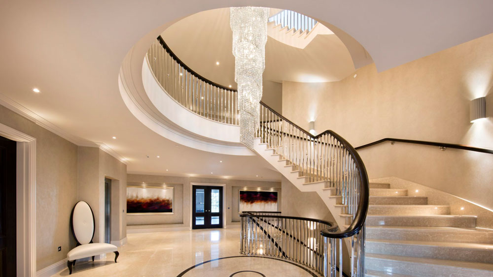 A spiral staircase in a grand entryway illuminated and accentuated by a draping spiral crystal chandelier, wall sconces, and recessed lights.