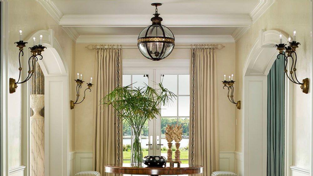 Traditionally decorated foyer interior with metal and glass orb pendant lights and coordinating candelabra wall sconces.