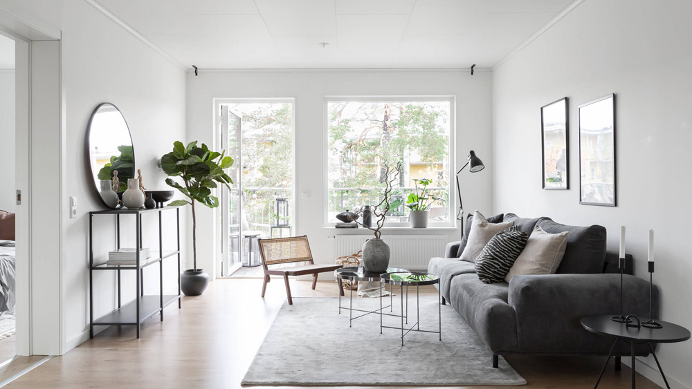 A BoKlok home's white living room, with a door that opens to the terrace and a large picture window, modern furniture and art from IKEA.