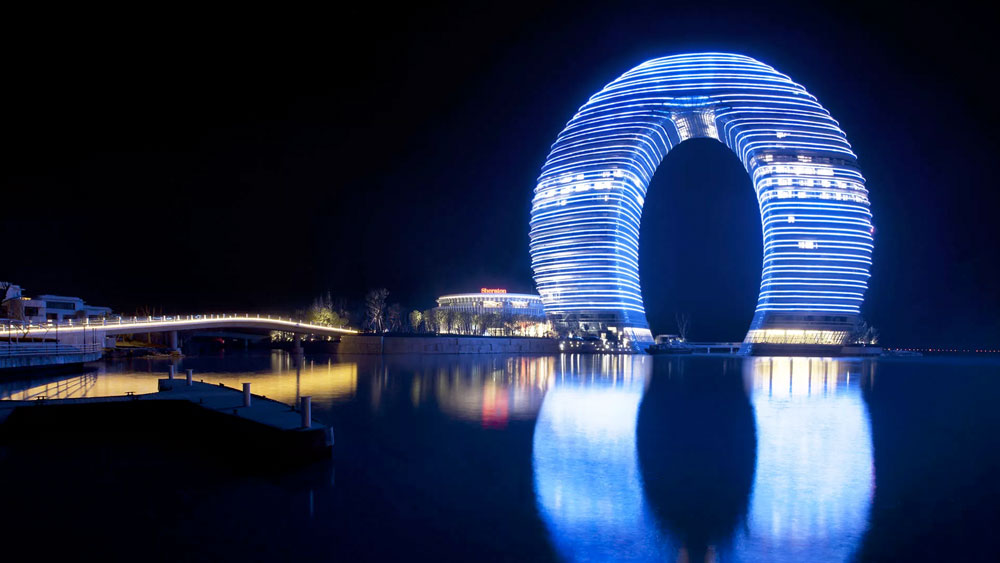 27-story, ring shaped Sheraton Hot Spring Resort in Huzhou, China lit blue at night with reflection on the water