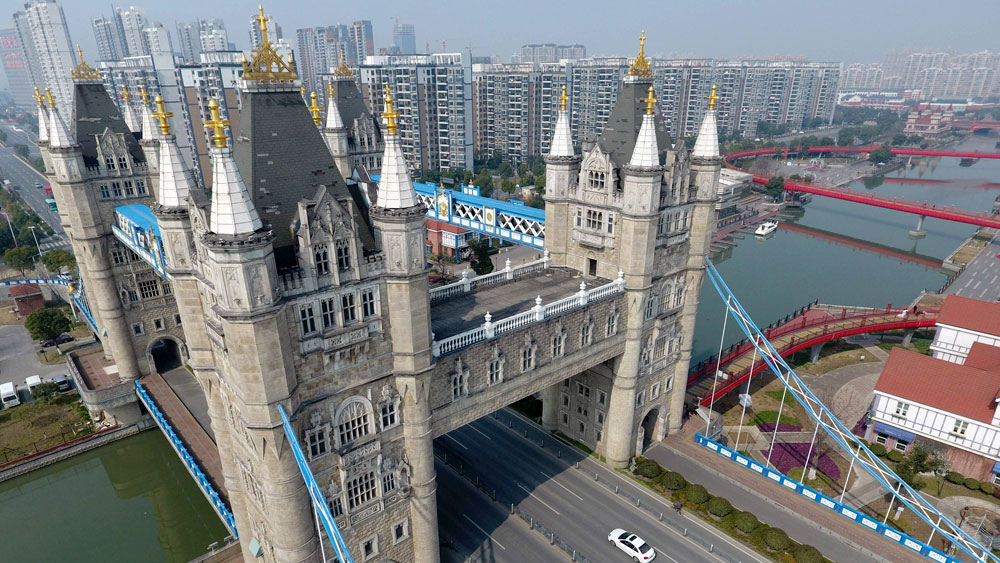 A replica of London's Tower Bridge in Suzhou, China shown with 4 turrets instead of the original 2 over a waterway with a cityscape in the background
