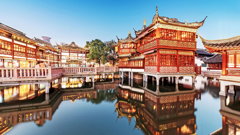 Yuyuan Garden in Shanghai displaying Intricately carved wood and sweeping rooflines over a waterway