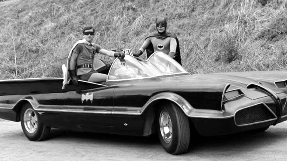 1960's Batman and Robin standing by the Batmobile in front of Bronson Caves where they filmed scenes in front of the Batcave