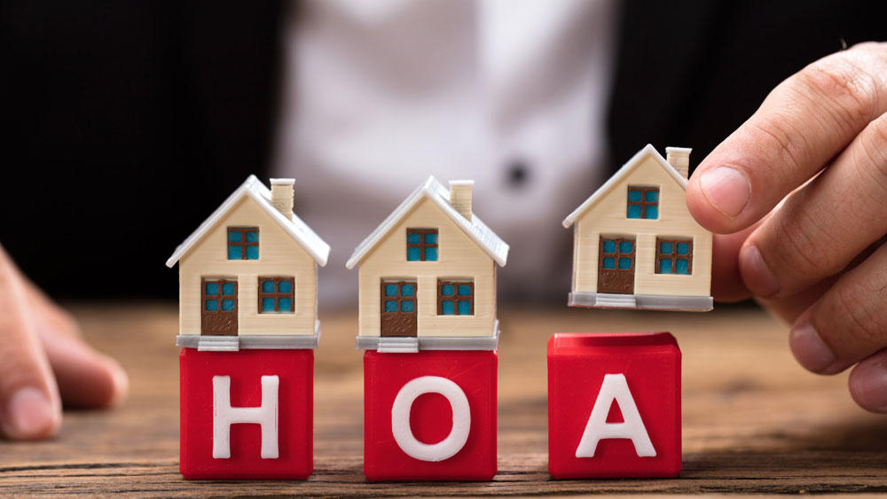 Tiny houses set atop red toy blocks with the letters HOA