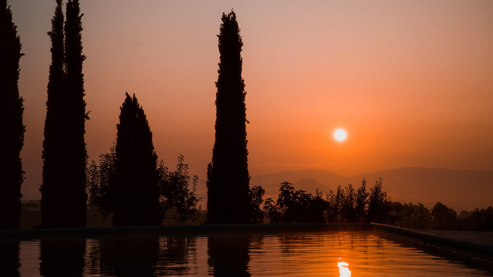 Bright orange Texas sunset reflected on water, capturing the natural beauty of the sunlight and surroundings on a lake-adjacent lot