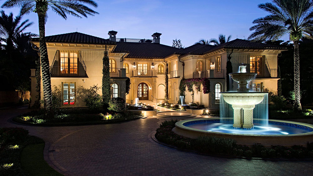 Evening exterior of stucco Mediterranean mansion in Naples, Florida with circular paver driveway surrounding a large fountain.
