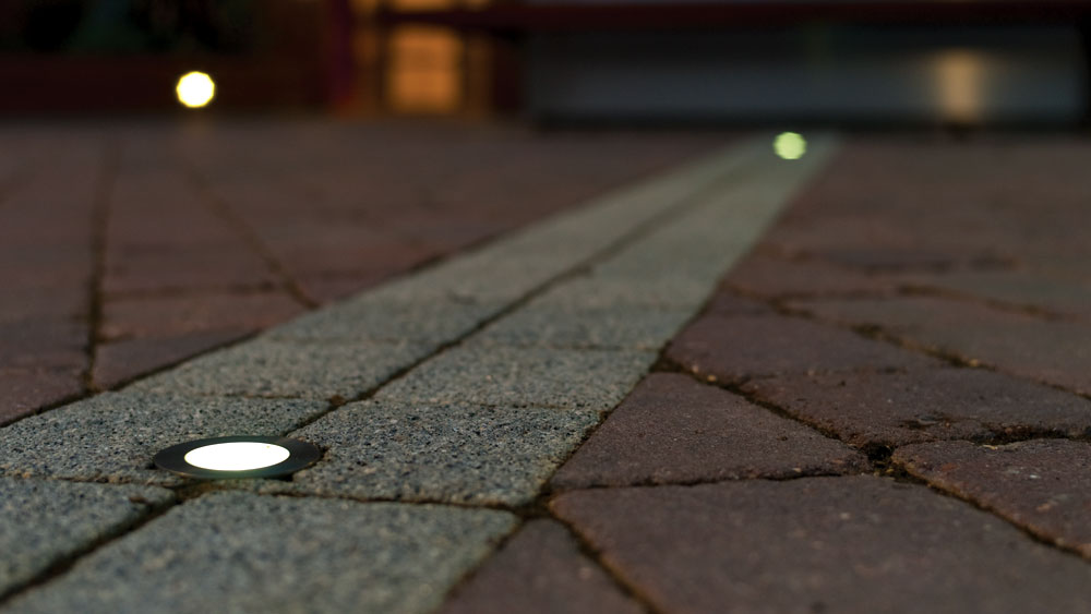 Night view of in-ground path lights leading up a residential driveway featuring WAC Lighting's Slim Recessed Luminaire.