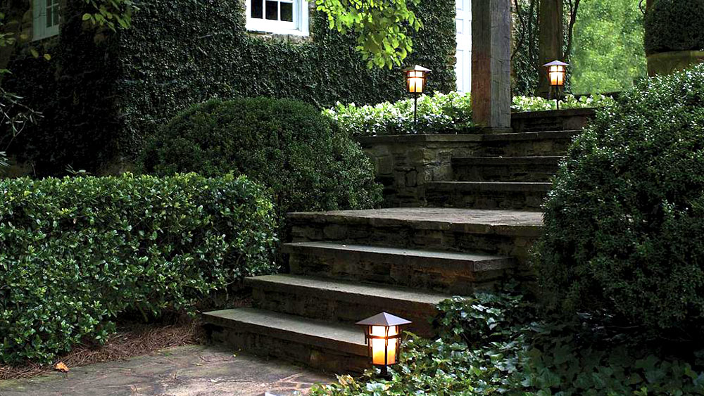 Photo of an ivy covered house and stone walkway, accented by the Hinkley Harbor post lantern path lights in a bronze finish.