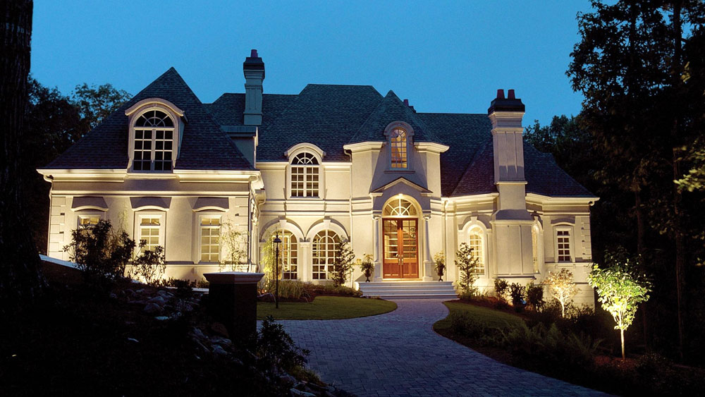 Evening exterior of a French traditional stucco home with wall-wash landscape lights from WAC Lighting.