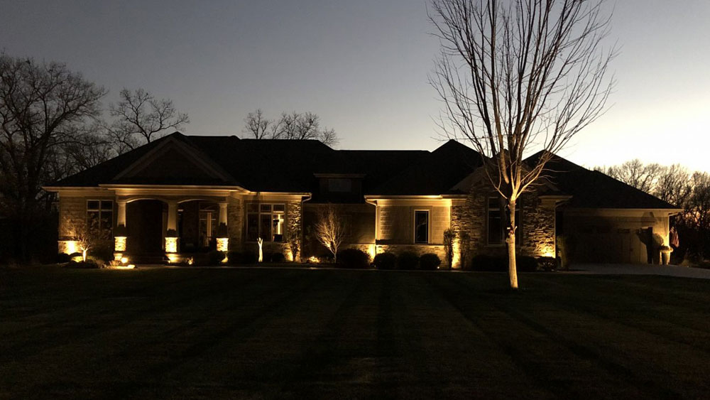 Exterior of a brick house at night with up-lighting that creates haunting shadows on the house