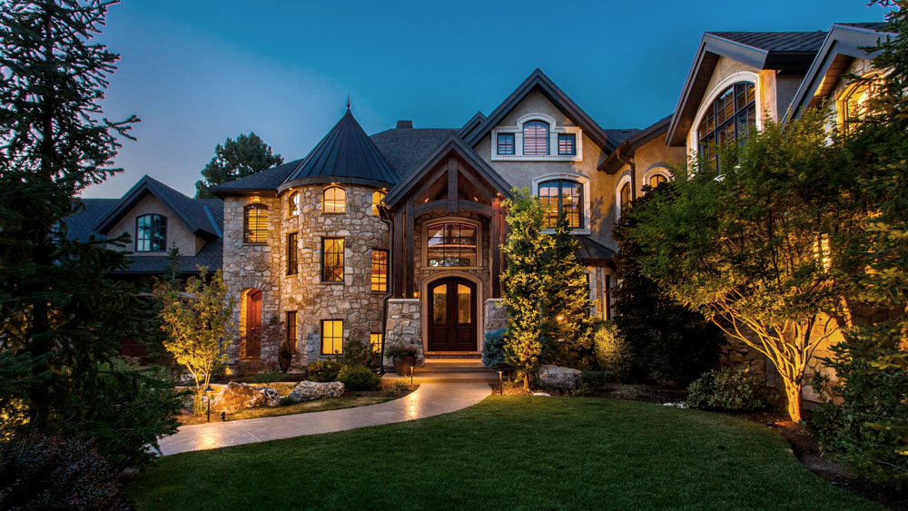 Stone and stucco estate exterior at night, lit by layered exterior lighting