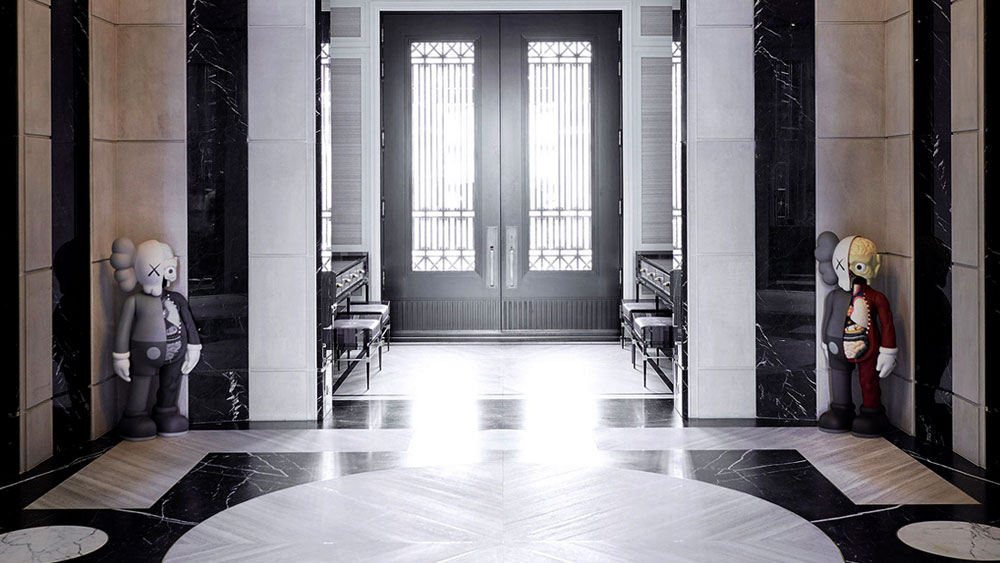 Sunlight floods through an iron double door in Drake's foyer into the custom designed Nero Marquina and Escarpment White marble inlaid floor.