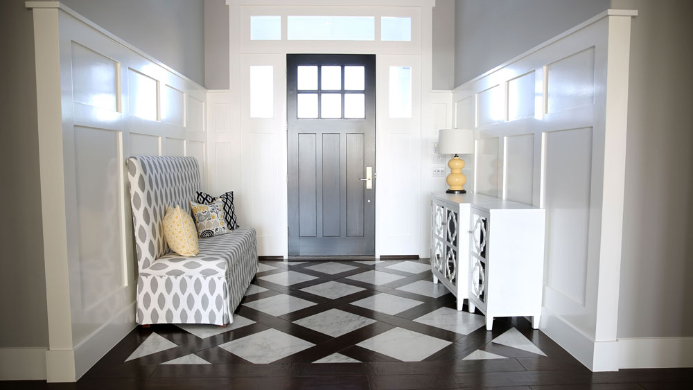 Bright traditional foyer with white paneled walls, black front door, and wide wood plank and marble flooring in a diamond pattern.