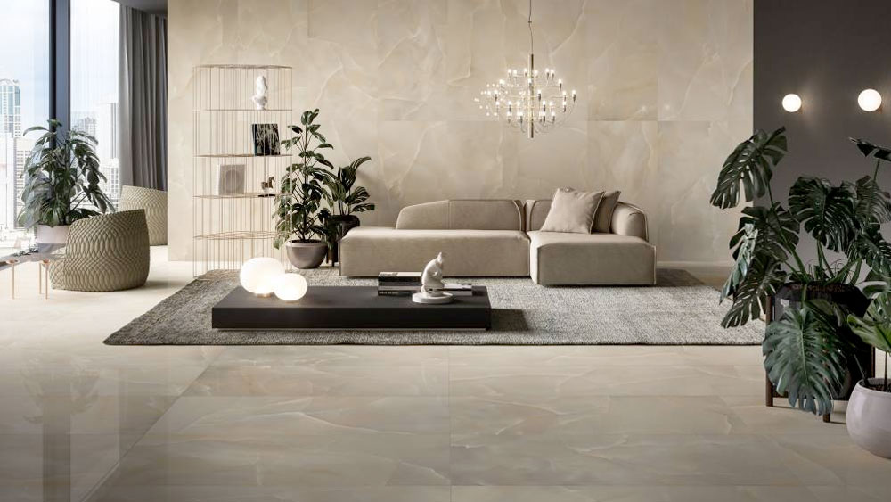 A sun-filled living room floor and walls tiled in a polished onyx porcelain from Refin's Prestigio Onyx line.