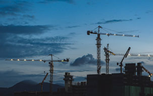 Multiple construction cranes lit up at dusk, signifying the slowdown in commercial construction activities since the onset of the pandemic.