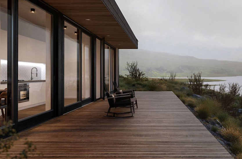 Organic modern home with ipe wood deck overlooking a lake with rolling hills in the background